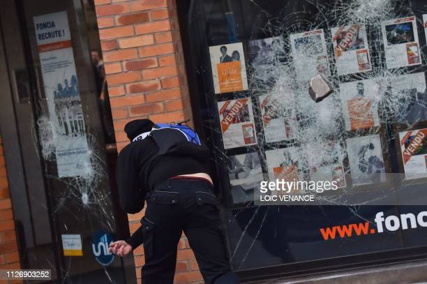 A man lobs a rock at a shop window as as members of the yellow vest take part in the 15th consecutive Saturday of demonstrations in Rennes western...