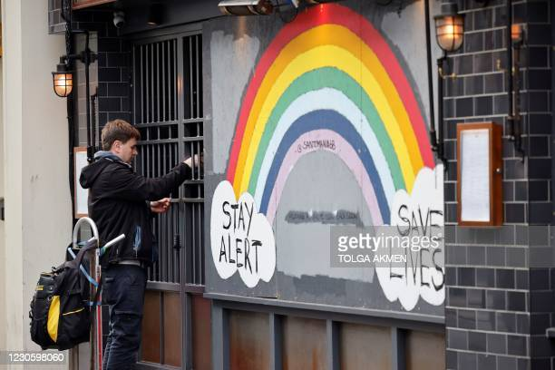 Man locks the security gate of a closed restaurant on Old Compton Street in Soho, central London on January 15 during the third nationwide...