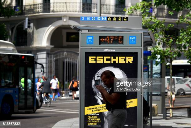 A man loights a cigarette in front of a city digital board indicating 47 degrees Celsius at a bus stop in Madrid during a heat wave on July 13 2017 /...