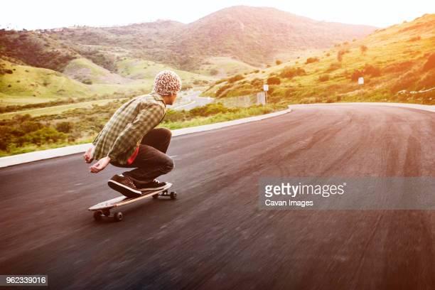 man longboarding on mountain road - eislauf oder rollschuhlauf stock-fotos und bilder