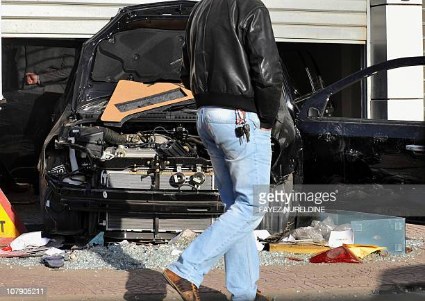 A man look at a destroyed car in a damaged car retailer in the Bab El Oued distric of Algiers' city center on January 6 after clashes between police...