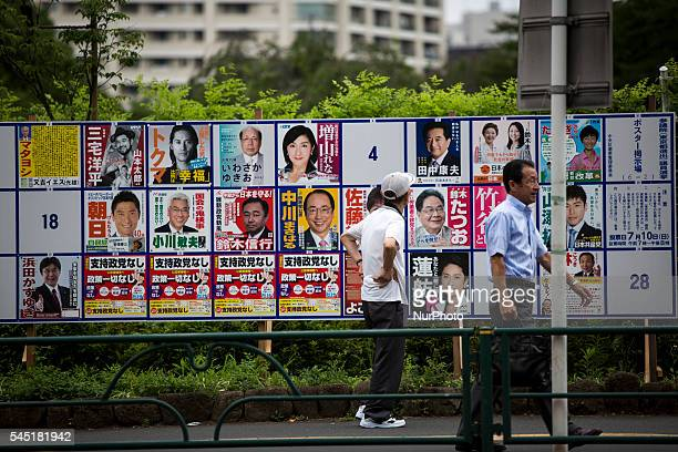 Man look at campaign posters with pictures of candidates for the 2016 Upper House election in Tokyo, Japan, on Tuesday, July 5, 2016. Japanese voters...