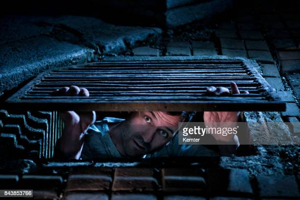 man looking afraid out of manhole at night - fugitive stock photos and pictures
