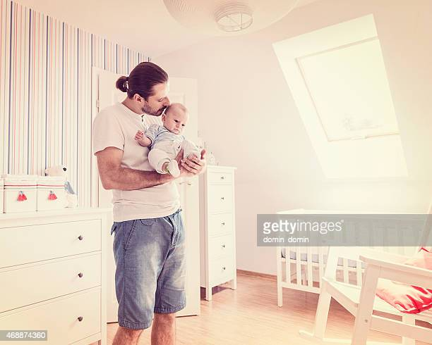 Man looking after baby boy, holding son on hands, retro