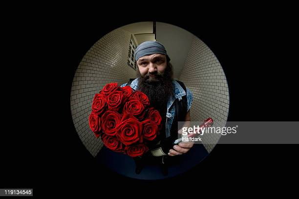 A man looking apologetic with roses and champagne viewed through a peephole