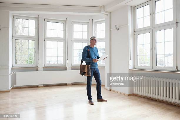 Man looking around in empty apartment