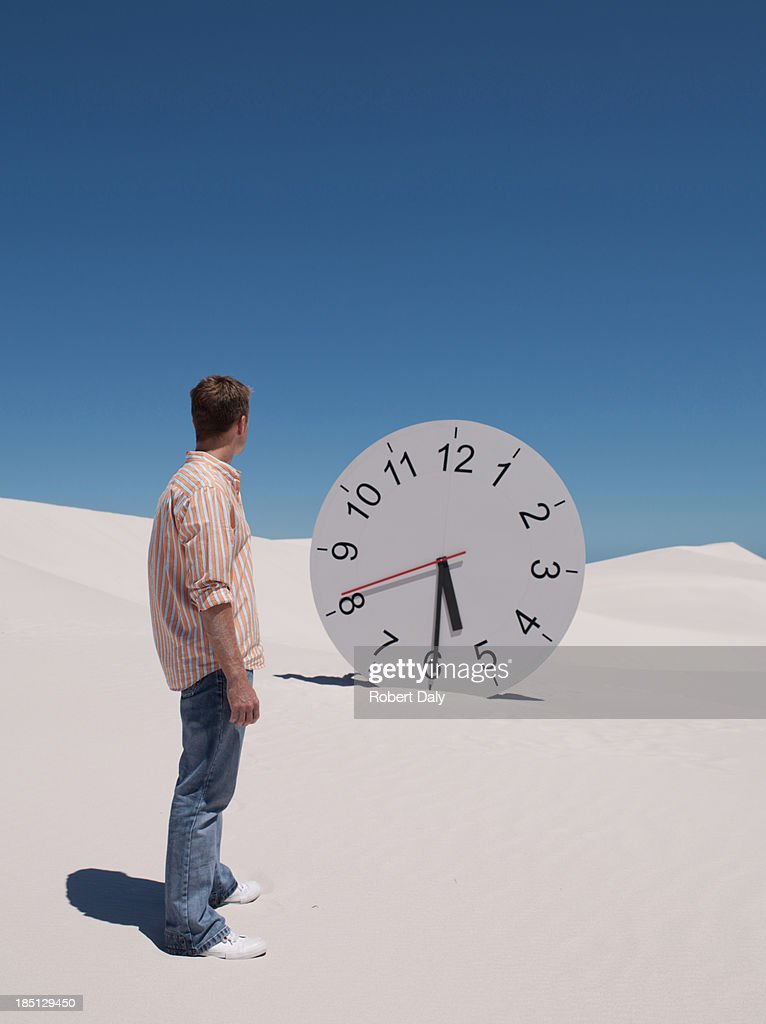 A man looking at a clock in the desert : Stock Photo