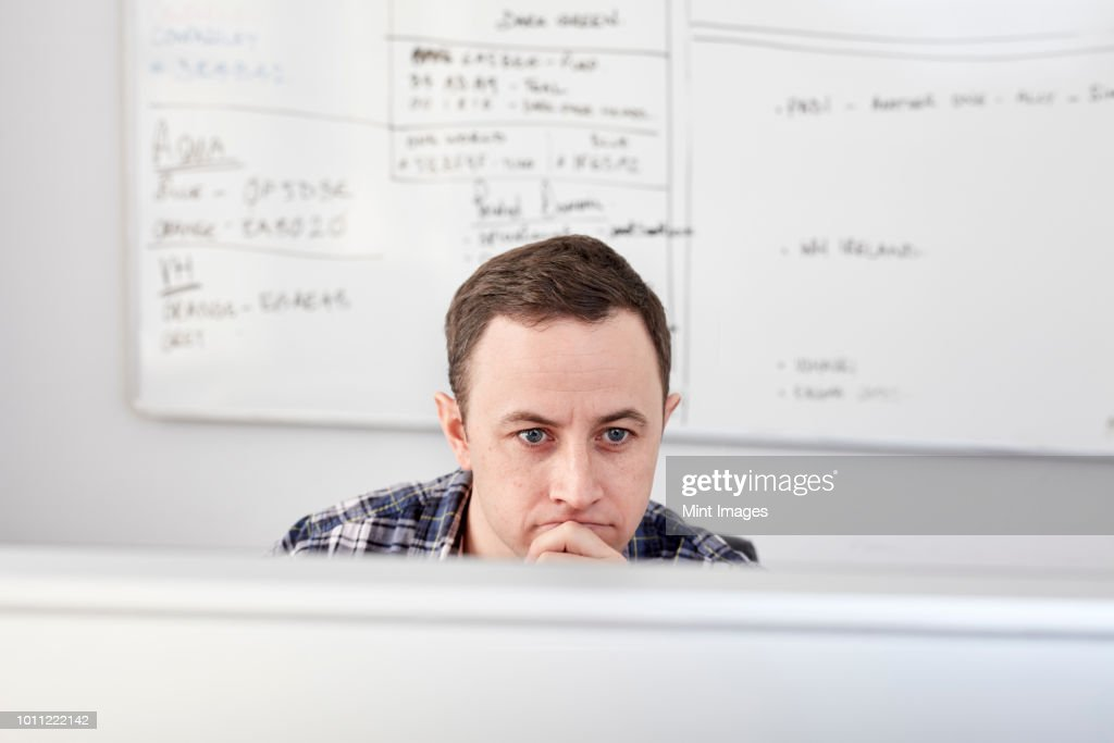 man looking at a computer screen seated at his desk with a project