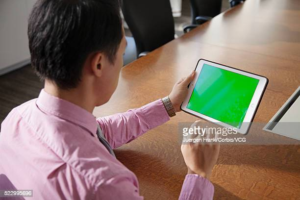 Man looking at a green screen on his tablet
