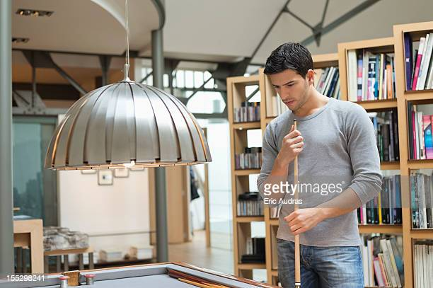 Man looking at a pool table