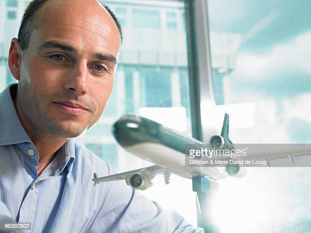 Man looking at a reduced plane model