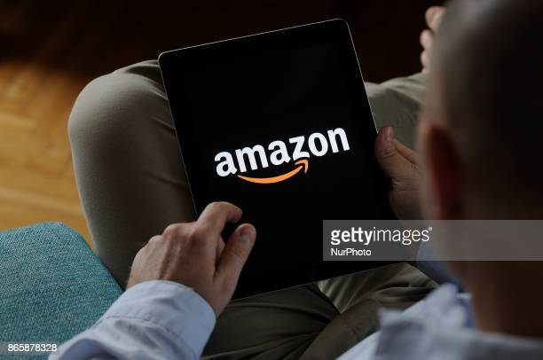 A man looking at a screen with an Amazoncom logo on an iPad on October 24 2017