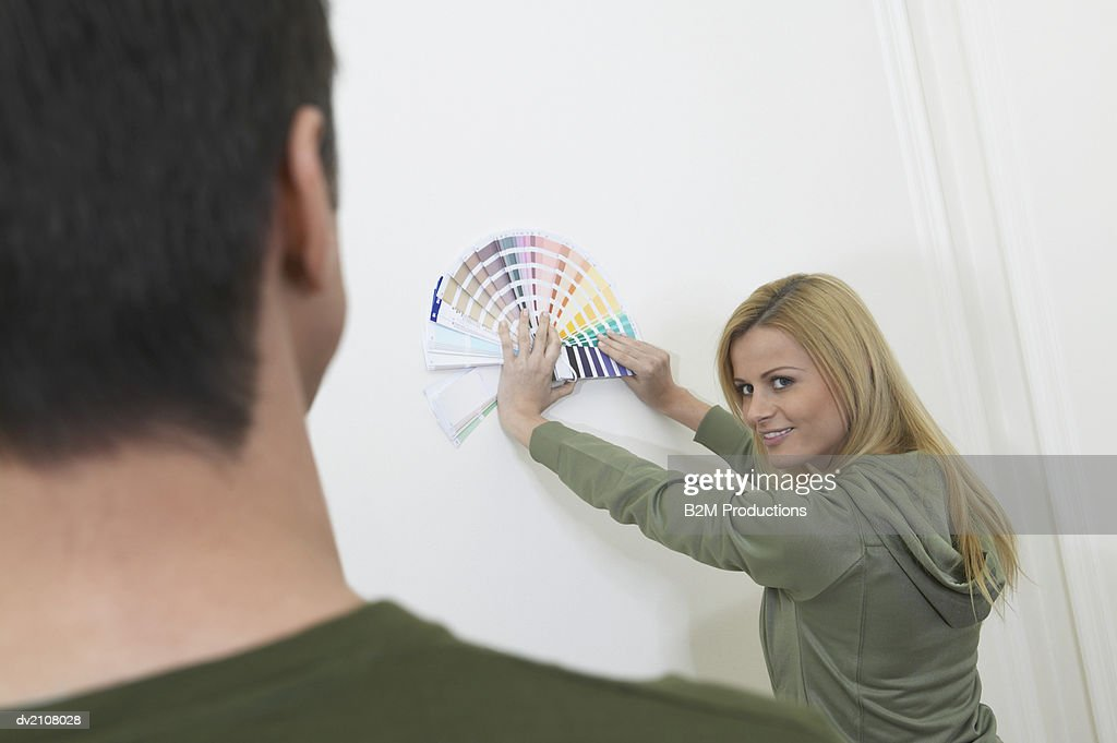 Man Looking at a Woman Holding Paint Swatches Against a White Wall : Stock Photo
