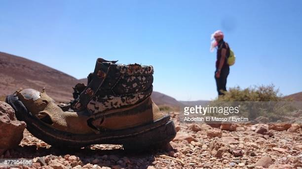 Man Looking At Abandoned Shoe Against Sky