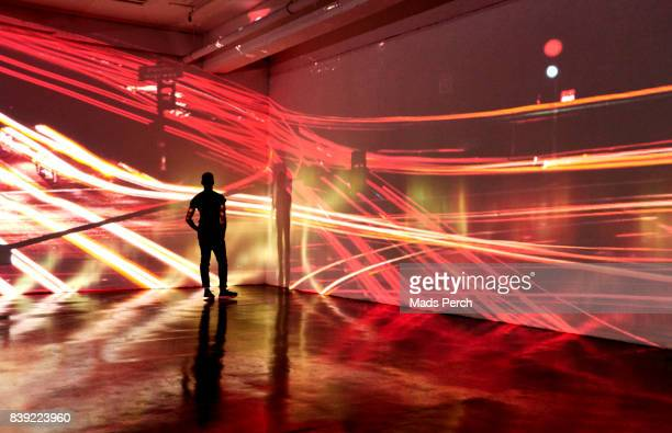 man looking at abstract nighttime cityscape being projected in gallery space - projektion stock-fotos und bilder
