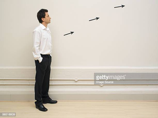 Man looking at arrows on a wall