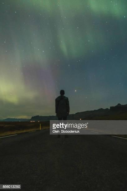 mann sucht bei aurora borealis - norden stock-fotos und bilder