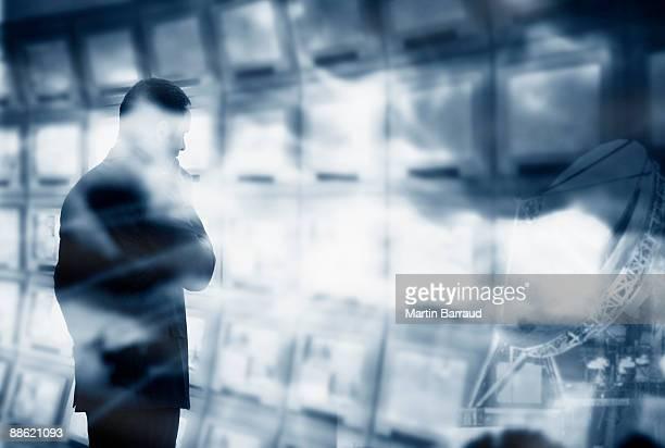 Man looking at bank of computer monitors
