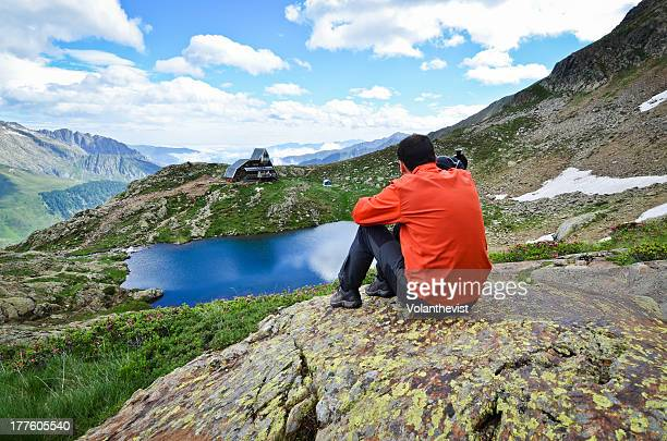 man looking at beautiful mountain landscape w lake - アリエージュ ストックフォトと画像