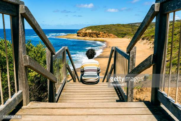 man looking at bells beach while sitting on wooden steps, victoria, australia - torquay,_victoria stock pictures, royalty-free photos & images