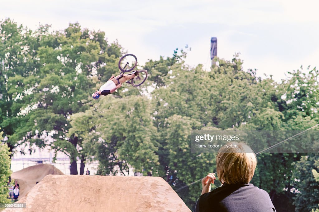 Man Looking At Bicycle Stunt Against Tree : Stock Photo