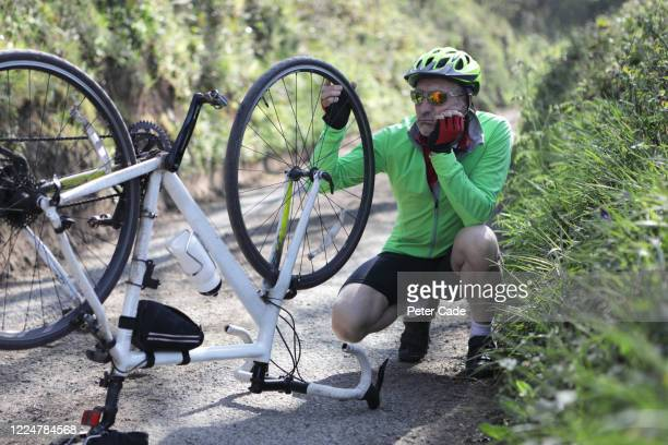 man looking at bicycle with damaged wheel - puncturing stock pictures, royalty-free photos & images