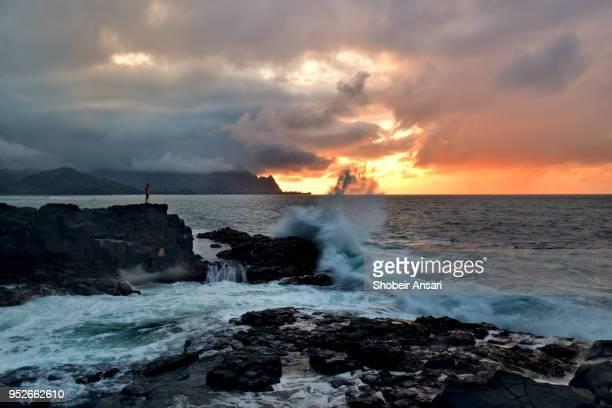 man looking at big wave splash, kauai, hawaii - seascape stock-fotos und bilder