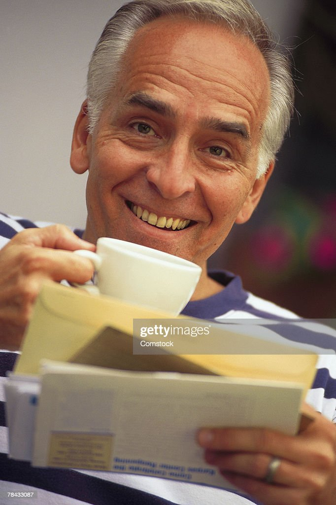 Man looking at bills while drinking coffee : Stockfoto