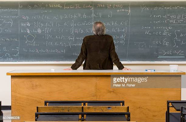 man looking at blackboard - mathematician stock pictures, royalty-free photos & images