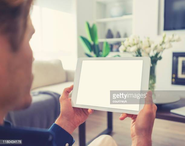 man looking at blank digital tablet. - over the shoulder view stock pictures, royalty-free photos & images