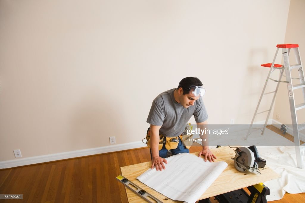 Man looking at blueprints for home improvement : Stock-Foto
