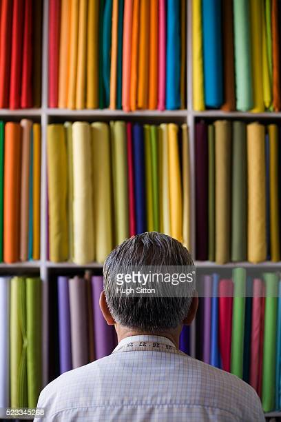 man looking at bolts of fabric - hugh sitton stockfoto's en -beelden
