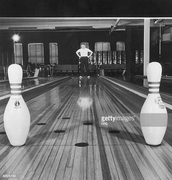 Man looking at bowling pins left standing in lane