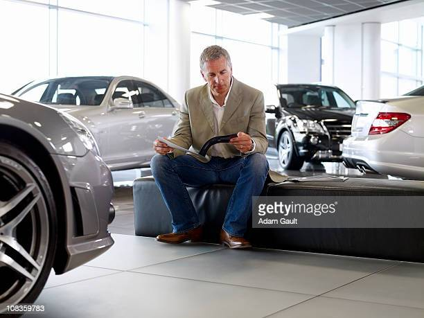 Man looking at brochure in automobile showroom