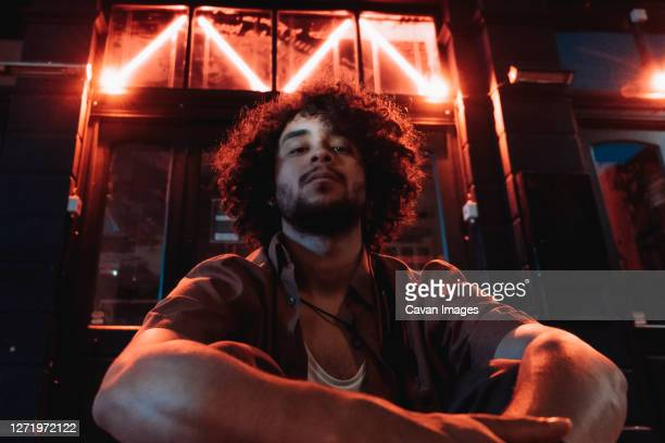 man looking at camera and neon lights - males stock pictures, royalty-free photos & images