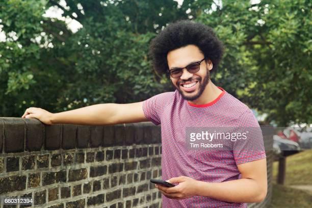 Man looking at camera holding smart phone
