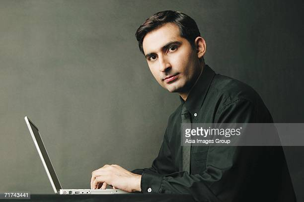 Man looking at camera, laptop open in front of him, portrait