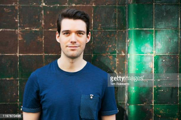 man looking at camera next to tiled wall - hair stubble stock pictures, royalty-free photos & images