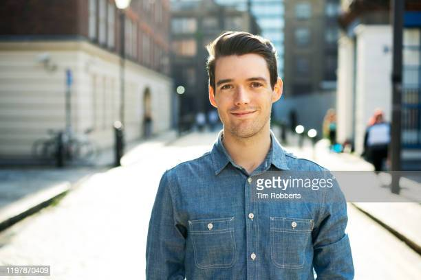 man looking at camera on street - caucasian ethnicity stock pictures, royalty-free photos & images