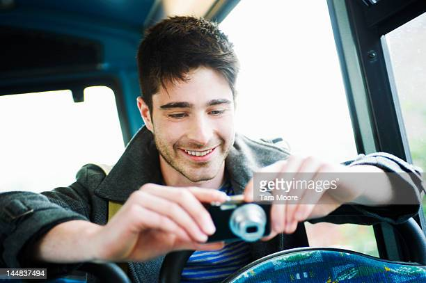 man looking at camera smiling on bus - newtechnology stock pictures, royalty-free photos & images