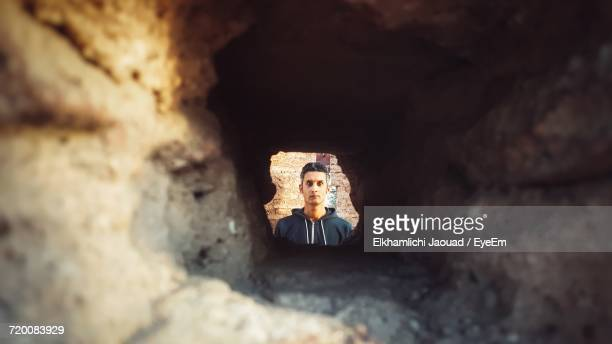 Man Looking At Camera Through A Hole In The Wall