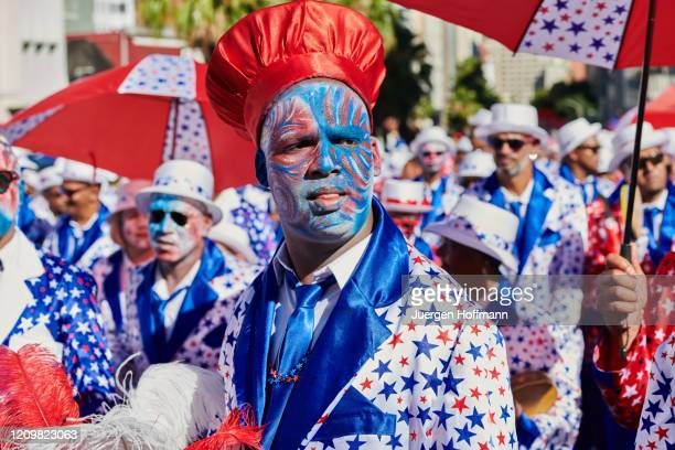 man looking at camera while people celebrating at kaapse klopse carnival in cape town - arts culture and entertainment stock pictures, royalty-free photos & images