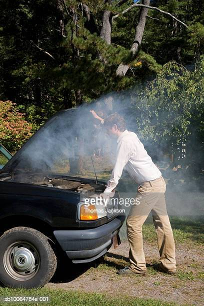 Man looking at car engine that is smoking on lawn