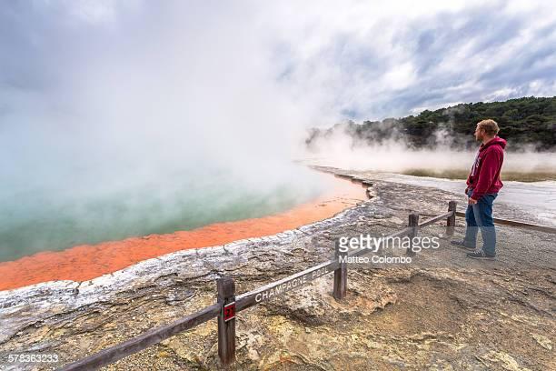 man looking at champagne thermal pool, rotorua - rotorua stock pictures, royalty-free photos & images