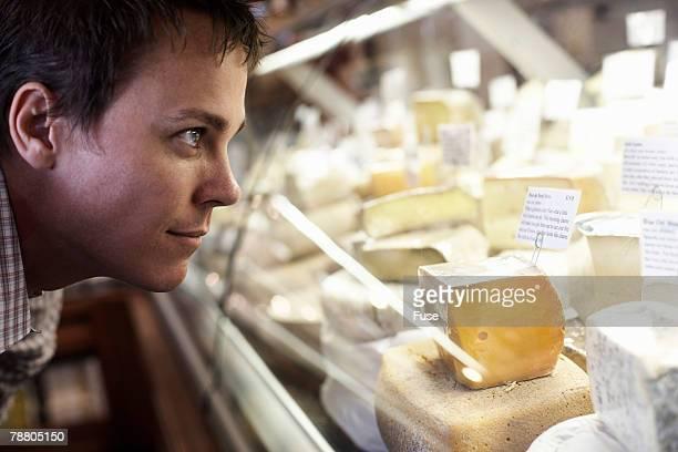 Man Looking at Cheeses