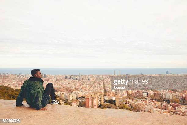 Man looking at cityscape while sitting on terrace