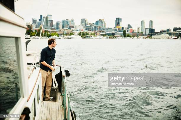 Man looking at cityscape while tying line on boat departing on cruise