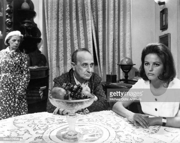 Man looking at Claudia Cardinale at table in a scene from the film 'The Magnificent Cuckold' 1964