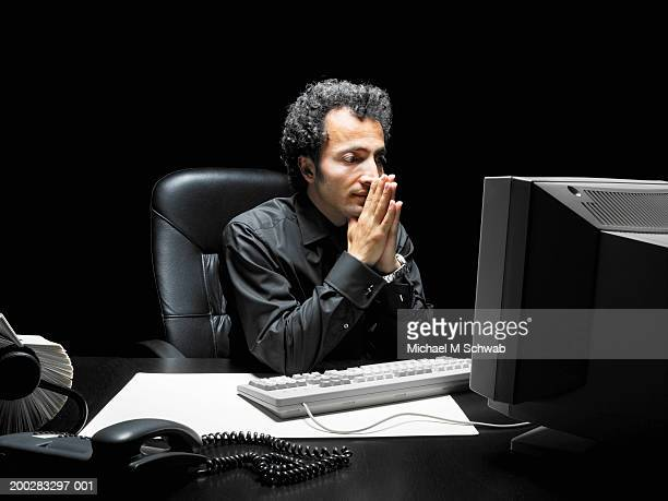 man looking at computer screen, hands in prayer position over mouth - michael turk stock pictures, royalty-free photos & images
