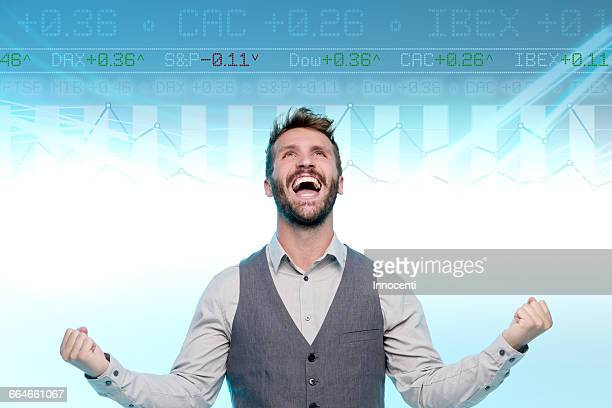 Man looking at data on graphical screen, fists clenched, excited expression